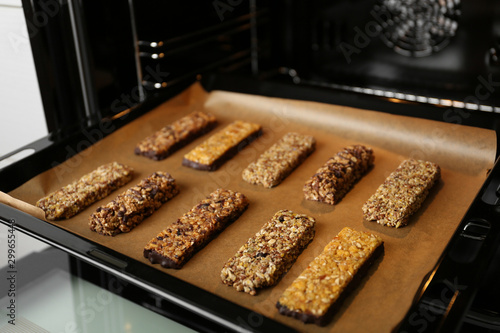 Obraz Delicious healthy granola bars on baking sheet in oven - fototapety do salonu
