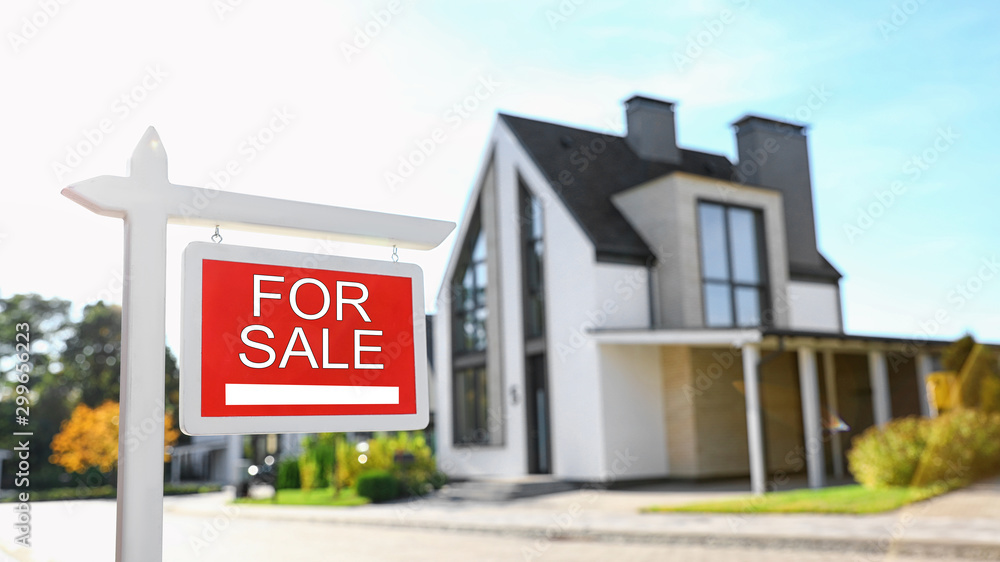 Fototapeta Red real estate sign near house outdoors on sunny day