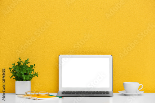 Modern laptop on desk near yellow wall, space for design. Home workplace