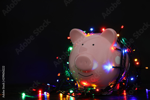Fotografía  Piggy bank with Christmas lights on wooden table against black background