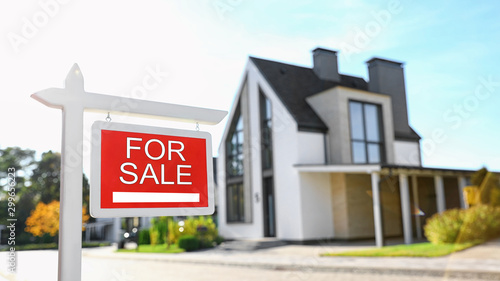 Obraz Red real estate sign near house outdoors on sunny day - fototapety do salonu