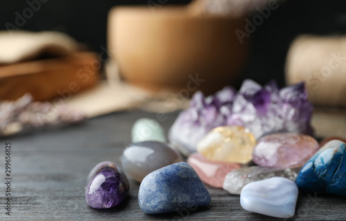 Many different gemstones on black wooden table