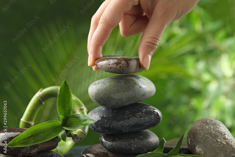 Fototapety, obrazy: Woman stacking stones against blurred background, closeup. Zen concept