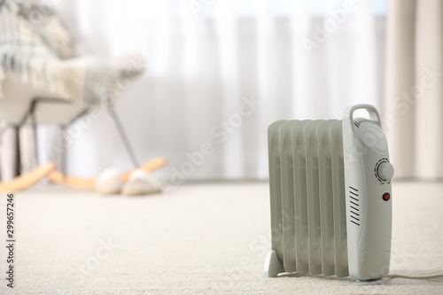Pinturas sobre lienzo  Modern electric heater on floor at home. Space for text