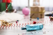 Empty Bottle And Confetti On Messy Floor. Chaos After Party