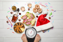 Woman Using Scale Surrounded By Food And Alcohol After Party On Floor, Top View. Overweight Problem