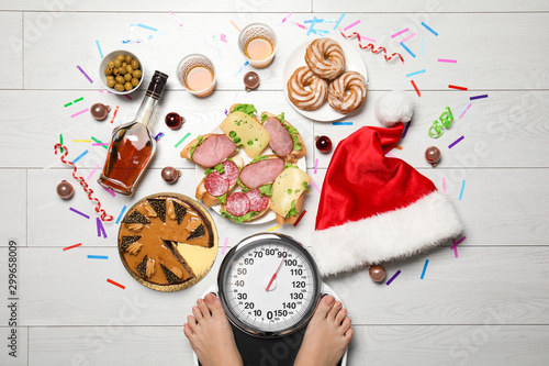 Fototapeta Woman using scale surrounded by food and alcohol after party on floor, top view. Overweight problem obraz