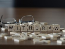 The Concept Of Withdraw Represented By Wooden Letter Tiles