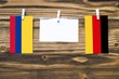 canvas print picture Hanging flags of Colombia and Germany attached to rope with clothes pins with copy space on white note paper on wooden background.Diplomatic relations between countries.