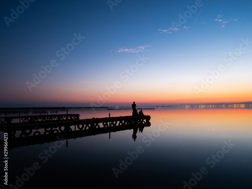 Tuinposter wooden jetty on salty lake and reflections in the water at sunset with orange colors