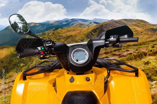 Foto auf Gartenposter Orange Atv vehicle standing on a mountain landscape offroad trail.