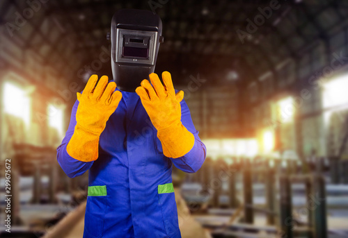 Valokuvatapetti Welder in orange gloves and mask standing in factory.