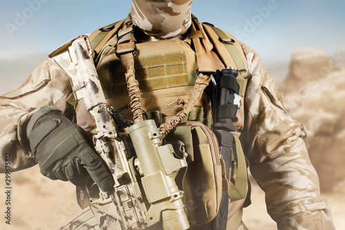 Photo  Soldier in uniform standing with rifle in desert.