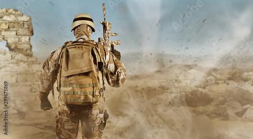 Soldier in uniform standing fully equipped rear view in desert. Canvas-taulu
