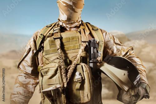 Valokuvatapetti Soldier in uniform standing in desert background with helmet.