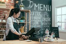 Portrait Of Young Cafe Owner Lady Using Cloth To Wipe Everything Before Opening Coffee Shop In The Morning. Girl Waitress Holding Rag Cleaning In Cafeteria. Colorful Tasty Macaron Dessert On Counter