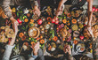Leinwanddruck Bild - Family or friends praying holding hands at Thanksgiving celebration table