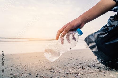 Hand picking up plastic bottle cleaning on the beach , volunteer concept Fototapeta