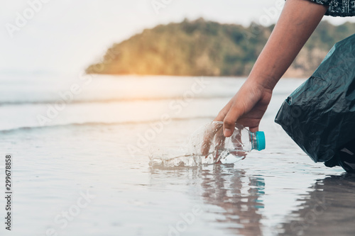 Fotografia Hand picking up plastic bottle cleaning on the beach , volunteer concept