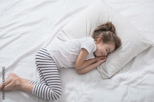 Photo  Cute little girl with long hair sleeping in bed.