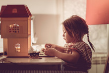 Girl Child With Pigtail Plays With Dollhouse