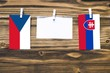 canvas print picture Hanging flags of Czech Republic and Slovakia attached to rope with clothes pins with copy space on white note paper on wooden background.Diplomatic relations between countries.