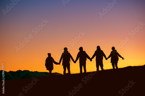 Silhouettes group of friends together at sunset