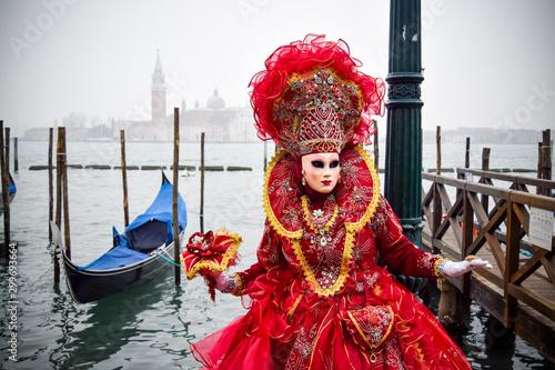 Obraz Masked Venetian Performer on Wooden Pier by Gondola in Venice, Italy - fototapety do salonu