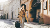 Fototapeta Uliczki - Female going with travel luggage at the narrow street between residential buildings in European town. Young girl rolling suitcase down on the cobblestone pavement and checking route on the paper map