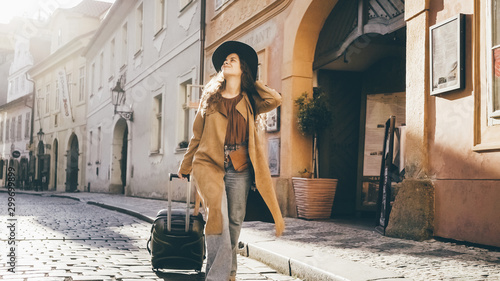 Female going with travel luggage at the narrow street between residential buildings in European town Fototapete