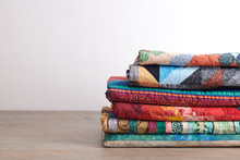 Quilts Stacked On Wooden Table...