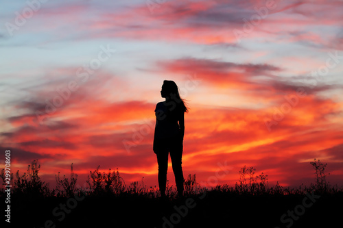 Fototapety, obrazy: Silhouette of a beautiful girl on a sunset background, incredible red sunset in the sky