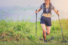 Woman Athlete Runner With Trekking Poles Running Up Mountain Trail Along The River