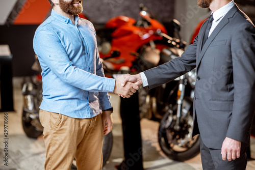 Fotografia, Obraz Handshake in the showroom with motorcycles