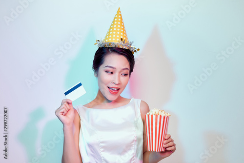 Portrait of young overjoyed attractive woman in white dress watching movie film, holding bucket of popcorn and credit card isolated on white background фототапет
