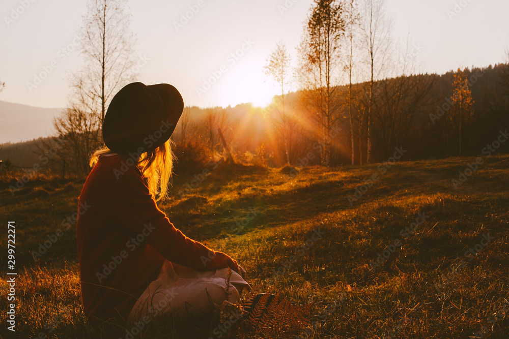Fototapeta A dreamy young girl or woman traveler in a fedora hat sits in the grass and enjoys the mountain view, the warm rays of the autumn sun and a beautiful sunset.
