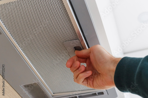 Fotografía  Man removing a filter from cooker hood for cleaning or service