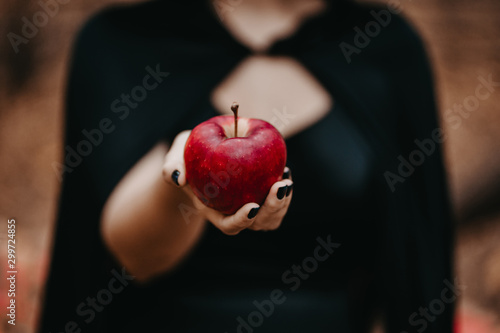 Fotomural Woman as witch in black offers red apple as symbol of temptation, poison