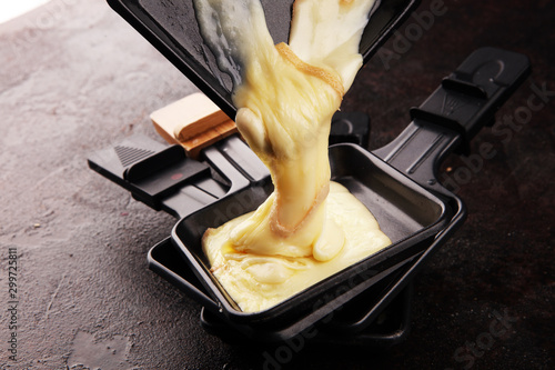 Fototapeta raclette cheese melted served in individual raclette skillets obraz
