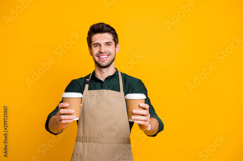 Portrait of positive cheerful guy worker in coffee bar shop hold paper card cup Wallpaper Mural