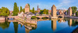 canvas print picture - Panoramic view of the Ponts Couverts (covered bridges), a medieval set of bridges and defensive towers on the river Ill at the entrance of the Petite France historic quarter in Strasbourg, France.