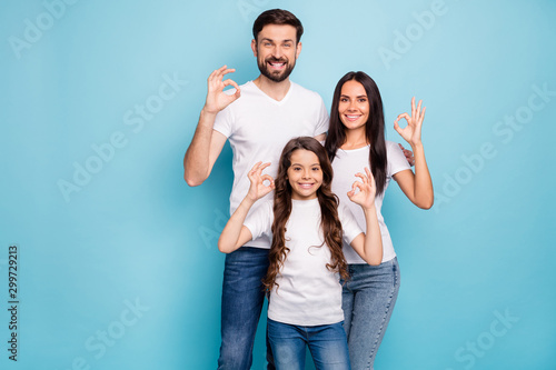 Poster Individuel Portrait of positive content three promoters mom dad offspring with brunet hair show ok sign recommend sales ads wear white t-shirt denim jeans isolated over blue color background