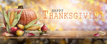 Thanksgiving Celebration Banner Of Pumpkins, Apples, Pears And Corncobs On The Left Hand Side Of A Table With A Wooden Background And The Words. Happy Thanksgiving On The Right.