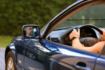 Kierowca za kierownicą samochodu osobowego, lusterko.