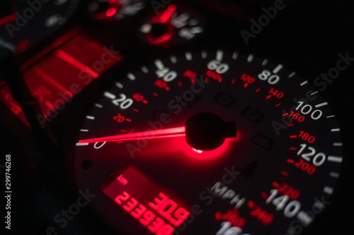 Fotomural  car dashboard. Speedometer with red backlight at night close up