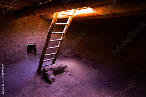 Photo Ladder with light descending into Pueblo Kiva in New Mexico.