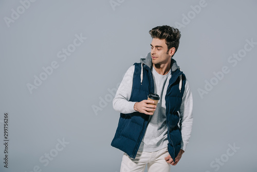 Fotomural  handsome pensive man in warm waistcoat holding coffee to go, isolated on grey
