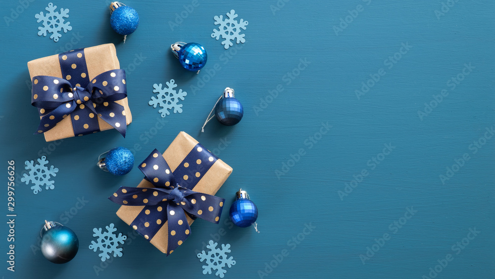 Fototapety, obrazy: Elegant Christmas composition. Flat lay gift boxes with blue ribbon bow, blue balls and snowflakes on blue background. Xmas banner mockup with modern decorations. Top view, copy space