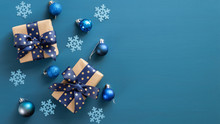 Elegant Christmas Composition. Flat Lay Gift Boxes With Blue Ribbon Bow, Blue Balls And Snowflakes On Blue Background. Xmas Banner Mockup With Modern Decorations. Top View, Copy Space