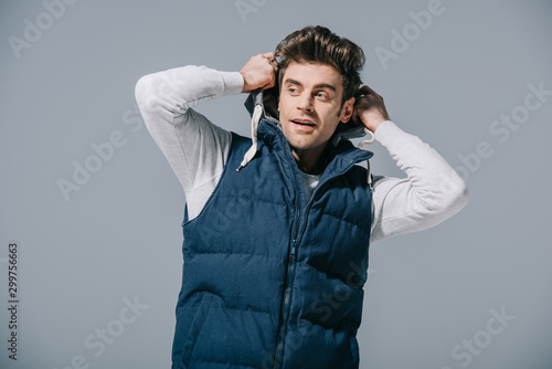 Fotografija handsome fashionable man posing in autumn waistcoat, isolated on grey
